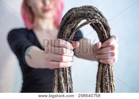 A hairdresser is is holding dreadlocks and pigtails poster