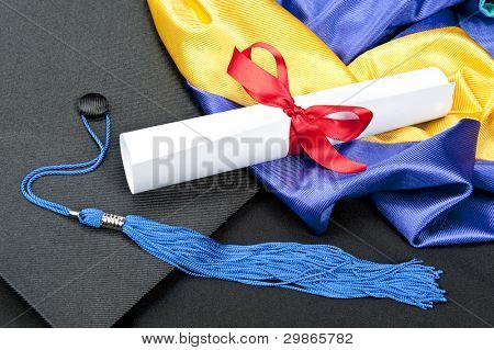 A graduation setting with cap,tassel, gown, hood and diploma.