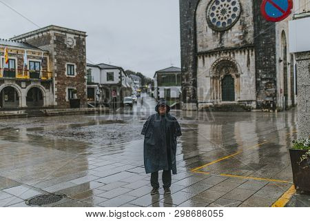Happy Senior Man Portrait With A Raincoat On, In Front Of A Romanesque Church During Camino De Santi