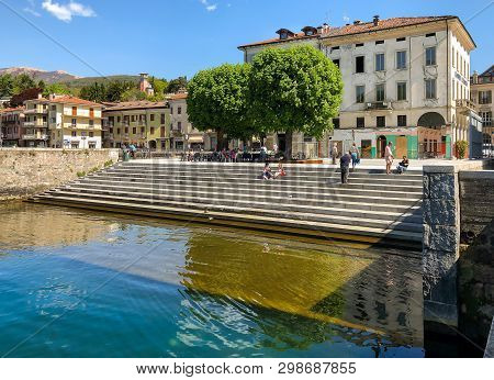 Luino, Lombardy, Italy - April 30, 2019: People Resting On The Lakefront Of Luino, Located On The Co