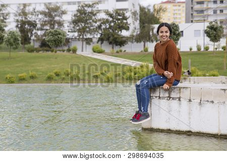 Happy Woman Sitting On Parapet By City River. Pretty Young Lady Looking At Camera And Sitting With L