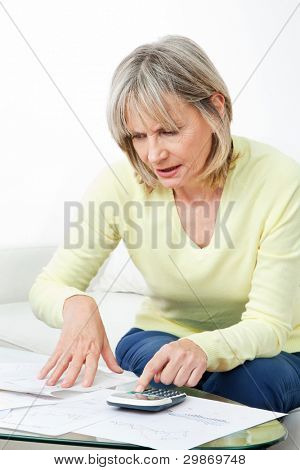Senior woman checking pension approval certificate with calculator at home