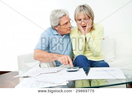 Worried senior couple sitting with bills and calculator at home