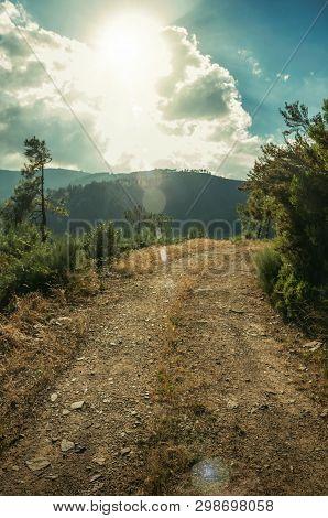 Dirt Road On Hilly Terrain In Sundown