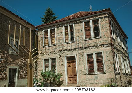 Old Two-story Stone House Behind A Metal Sculpture In Menorah Shape, In A Sunny Day At Belmonte. A C