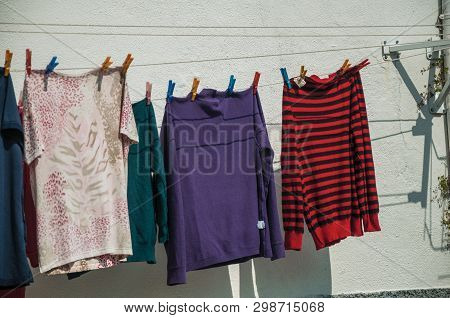 Colorful Clothes Hung To Dry In Front Of Building With Old Whitewashed Wall, In A Sunny Day Gouveia.