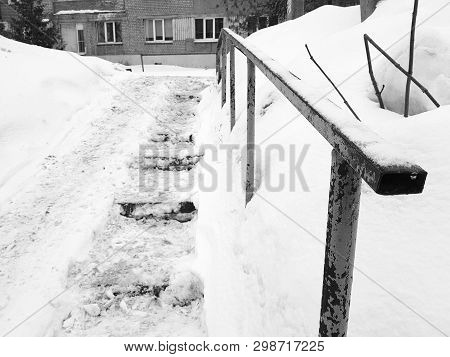 Dangerous slippery stairs and old handrail in the winter in the snow poster