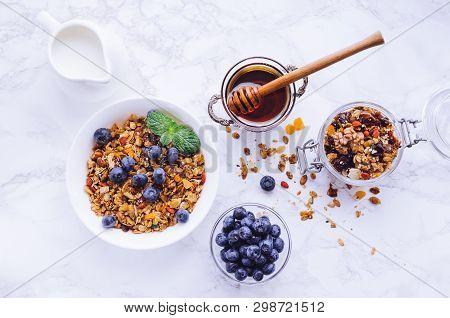 Bowl Of Homemade Granola With Milk, Honey And Fresh Berries On White Marble Table. Muesli Breakfast.