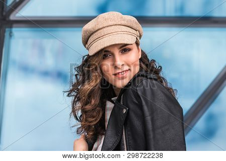 Fashionable Young Woman Posing Against Glass Windows Outdoors. She Is Smiling And Looking At Camera.
