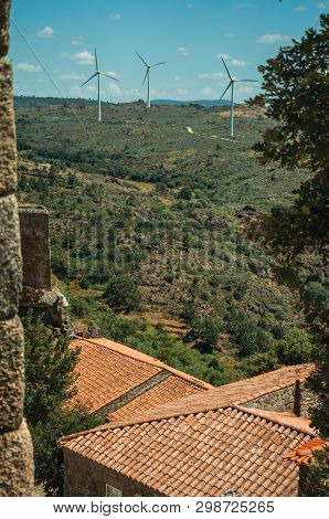 Wind Turbines For Electric Power Generation Over Hilly Landscape And Rooftops, Seen By Crenel At The