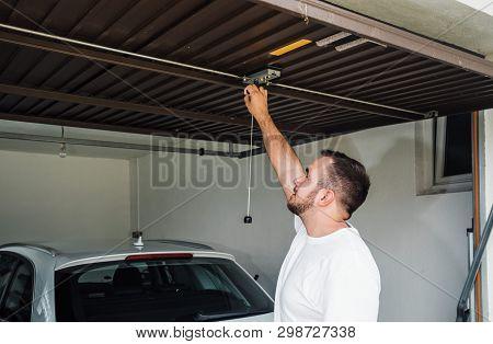 Iron Garage Door. Man Opens Garage Door Made Of Sheet Metal