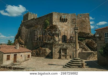 Stone Castle With Tower Over Rocky Hill And Old House Encircling Square With Pillory, In A Sunny Day