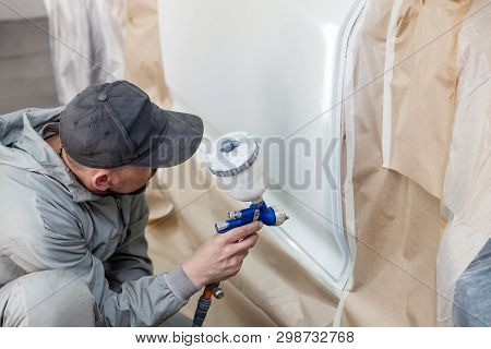 A Guy Worker Paints With A Spray Gun A Part Of The Car Body In White After Being Damaged At An Accid