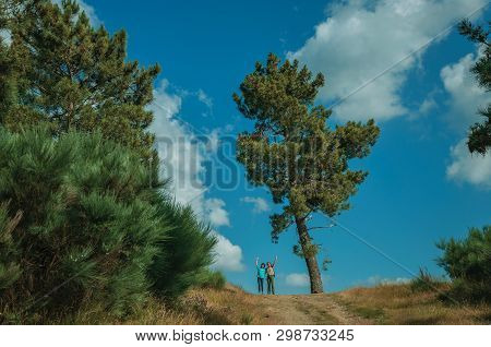 People Waving On Dirt Road With Tree