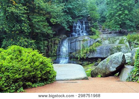 A Picturesque Cascade Waterfall Among Large Moss Covered Stones In The Landscape Sophia Park, Uman,
