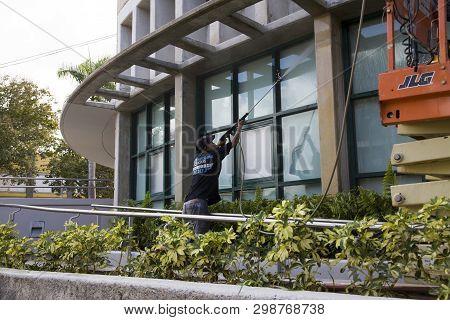 Bayamon/puerto Rico - February 26, 2019: Hispanic Man Uses High Pressure Washer Machine To Clean Ext