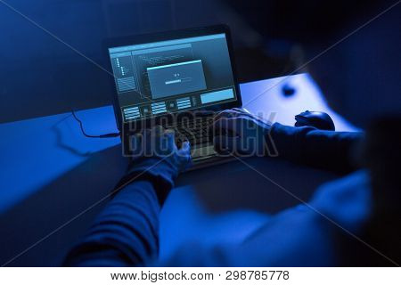 cybercrime, hacking and technology concept - hands of hacker with progress loading bar on laptop computer screen making cyber attack in dark room