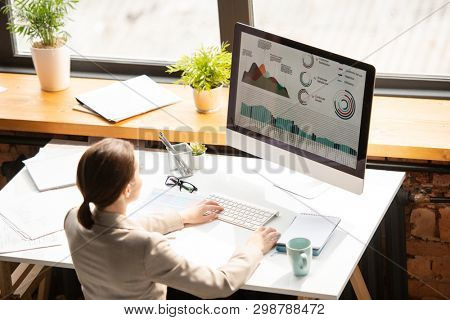 Contemporary young female analyst or economist in formalwear sitting by desk in front of computer monitor and working with charts and diagrams