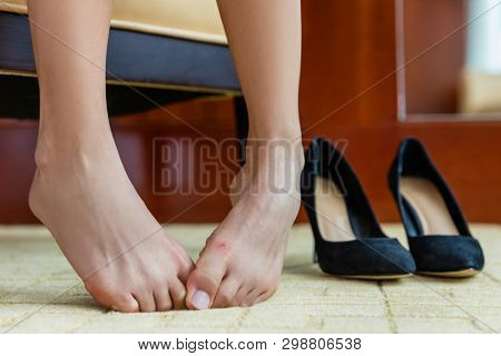 Tired woman removing high heels off feet. Shoe pain concept. Closeup of barefoot lady with painful toes - medical foot problem, nails or discomfort at store or home. poster
