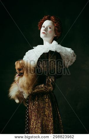 Sign of royalty. Medieval redhead young woman in golden vintage clothing as a duchess holding puppy and standing on dark green background. Concept of comparison of eras, modernity and renaissance. poster