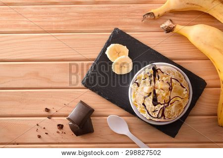 Banana Ice Cream Cup Decorated With Chunks And Syrup Chocolate And Slices Of Banana On A Plate On A