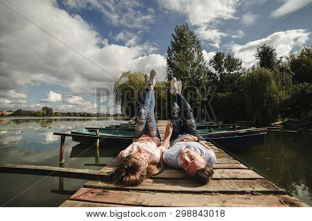 Perfect Date. Beautiful Young Couple And Smiling While Lying On The Pier. Happy Young Man And Woman