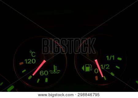 Close up shot of a car's coolant temperature and fuel gauge. poster