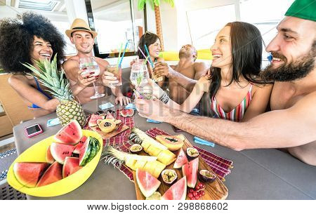Happy friends drinking fancy cocktails at boat party trip - Young millenial people having fun on luxury vacation - Travel lifestyle concept with millennials sharing aperitif drinks with tropical fruit poster