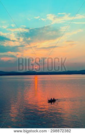 Sea tropic landscape. Sea water surface lit by sunset light. Summer sunny tropic water scene with unidentified people in the boat, concept of summer sea activities. Sea summer nature