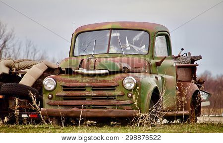 An Old Green Pickup Sits Beside A Pile Of Junk In A Field.
