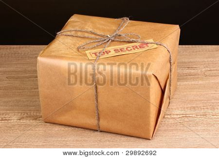 Parcel with top secret stamp on wooden table on brown background