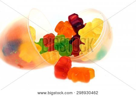 THC and CBD Gummy candies. Medical and Recreational Gummy candies. room for text. Marijuana Infused Gummy Candy in a Clear Easter Egg. Isolated on white. Room for text.