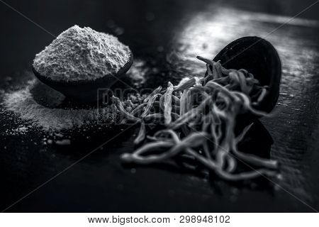 Popular Indian & Asian ayurvedic organic herb musli Safed Moosli/ Shaqaqule/ Dholi Musli/ Khiruva/ Shedheveli/ Swetha Musli/ Taniravi Thang/ in a clay bowl on wooden surface with its powder also. poster