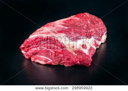 Raw dry aged wagyu beef clod roast as closeup on black background with copy space