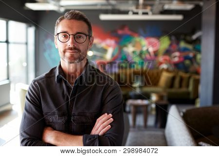 Middle aged white male creative in casual office lounge area looks to camera, arms crossed, waist up