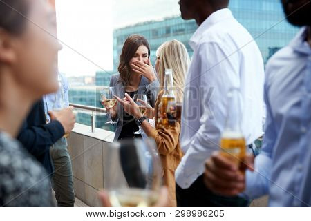 Office colleagues socialising with drinks on a balcony in the city after work
