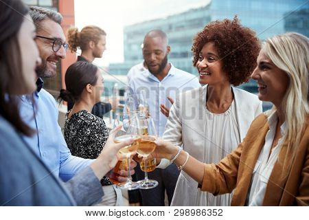 Socialising office colleagues raising glasses and making a toast with drinks after work