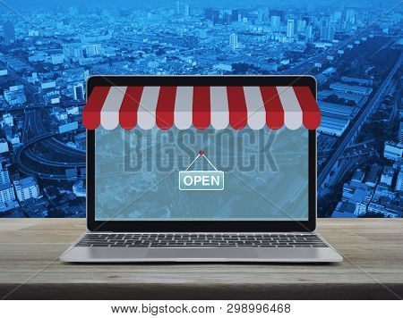 Modern Laptop Computer With Online Shopping Store Graphic And Open Sign On Wooden Table Over City To
