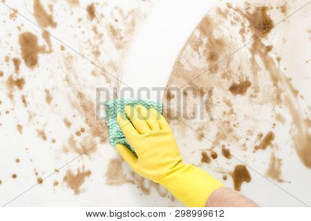 Gloved Hand Wiping Clean A Messy Counter Top Or Floor With A Cloth Or Rag
