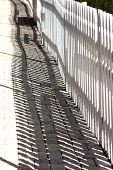 white picket fence with shadow on pavers poster