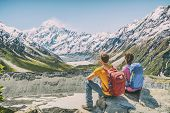 Backpackers couple hiking looking at Mount Cook view on mountains tramping in New Zealand. People hikers relaxing during hike in alps of south island. poster