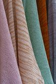 Details of several pieces of soft natural colored knitwear hanging in soft daylight poster