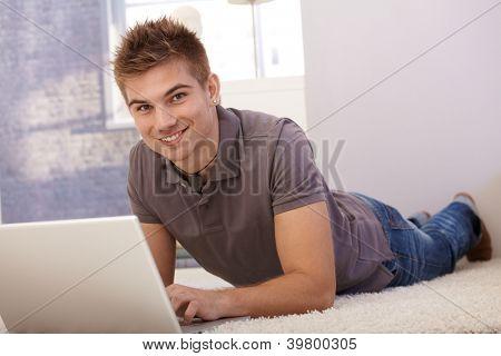 Porträt von happy Boy mit Laptop-Computer am Boden des Wohnzimmers, lächelnd in die Kamera.
