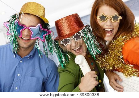 New year celebration in office, office workers in party hat and funny sunglasses having fun.
