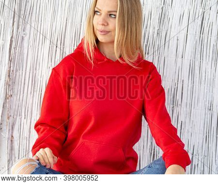 Smiling blond woman wearing red blouse or hoodie sits in front of camera. On her hoodie in place for christmas inscription. Winter outfit with copy space for mockup.