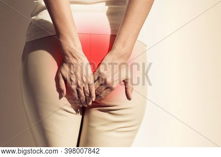The Pain Caused By Hemorrhoids. Woman Suffering From Hemorrhoid. Woman Hands Holding Her Butt Becaus