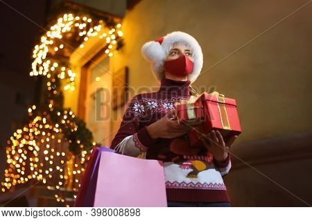 A Girl Wearing A Protective Mask Holds Gift Boxes And Bags As She Leaves The Store During The Covid-