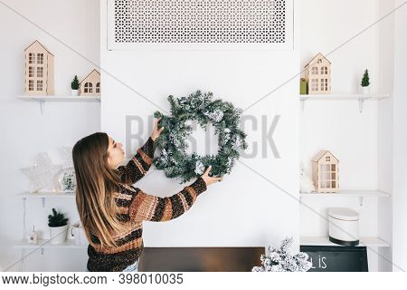 Young Woman Decorates The House For Christmas, Hangs A Wreath On The Wall. High Quality Photo