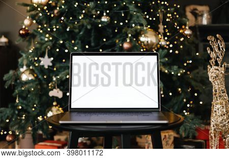 Laptop Computer With White Blank Screen Mock Up, On The Table Near Christmas Tree. High Quality Phot