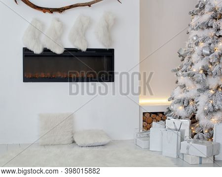 White Fireplace Is Decorated With Christmas Socks In Living Room. Empty Stockings Hung On Fireplace